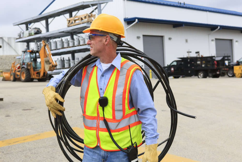 Engineer at electric power plant carrying coil of wire over shoulder at storage area