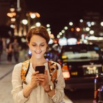 Smiling woman texting for Uber at the street
