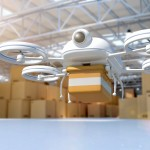 Composite image of a 3D generated model of a remote controlled drone taking off from a distribution warehouse full of cardboard boxes and goods. Drone is carrying a package for remote delivery: technology innovations allow quick shipping and delivery. The quadricopter has a camera and GPS to follow the route to destination. Drone model is white, carrying a brown yellow box.