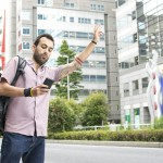 A young white italian man with tattoos, hailing a taxi whilst holding a cellphone in Tokyo.