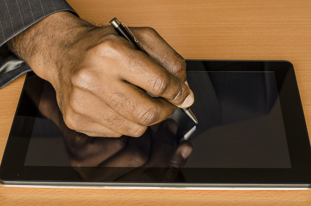 hand of a black man writing on an electronic tablet