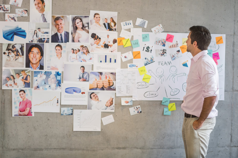 Young man working in a creative business looking at a wall chart