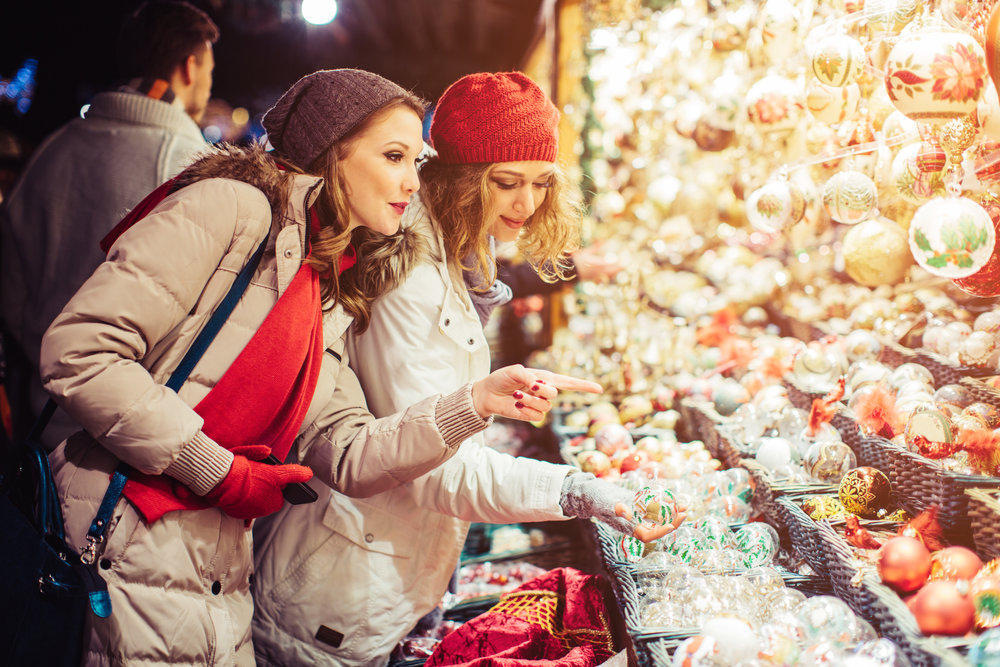 Friends shopping at christmas fair outdoors At Rathausplatz, Vienna, Austria. Wearing warm clothes, hats and scarfs. Looking at christmas decorations. Evening or night with beautiful yellow lights lightning the scenes.