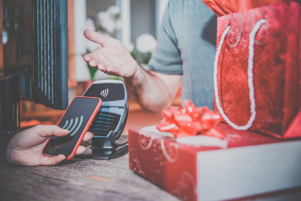 DSLR picture of a woman arm paying christmas or holiday gifts with a smart phone using NFC or contactless payment technology.