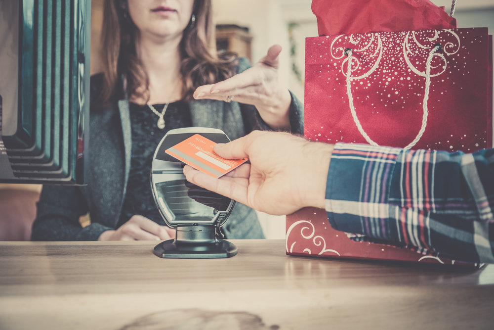 DSLR picture of a man arm paying christmas or holiday gifts with a credit card using NFC or contactless payment technology.