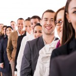 Group of business people standing in a row. Focus is on young happy businessman looking at the camera. Isolated on white.