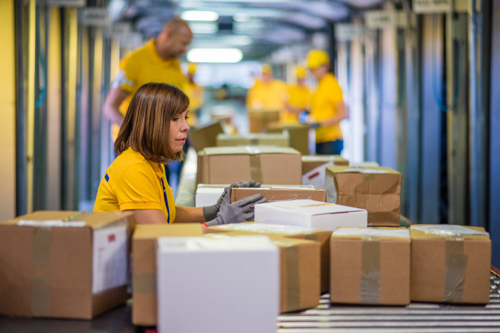 Woman processing boxes on conveyor belt in distribution warehouse.