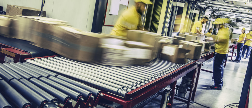 Group of distribution warehouse workers sorting packages that are moving on a conveyor belt. Blurred motion.