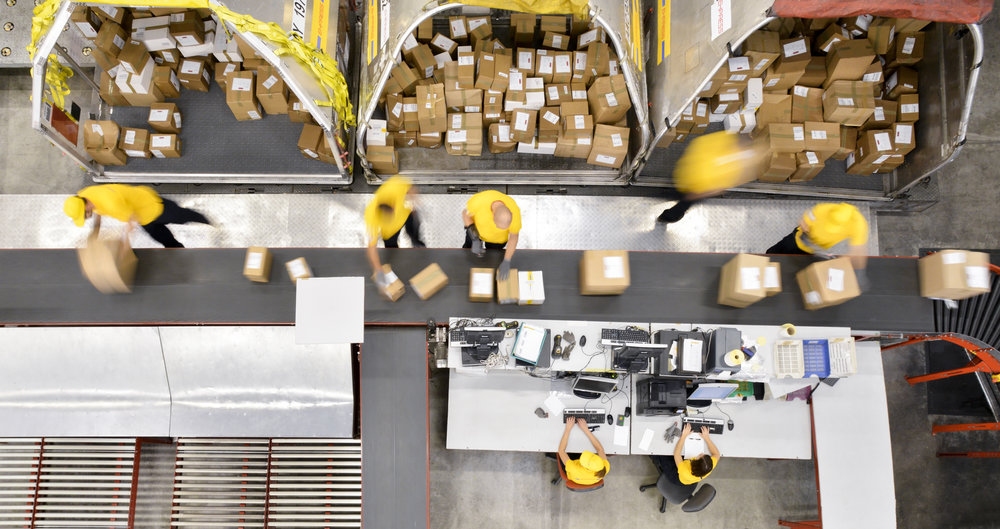 Workers processing boxes on conveyor belt in distribution warehouse, blurred motion.