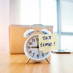 A clock with tax time sticky note on office table